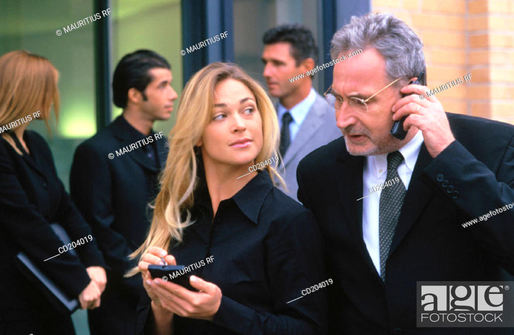 Stock Photo: Businessman talking on cell phone, businesswoman with organizer, three businesspeople in the background.