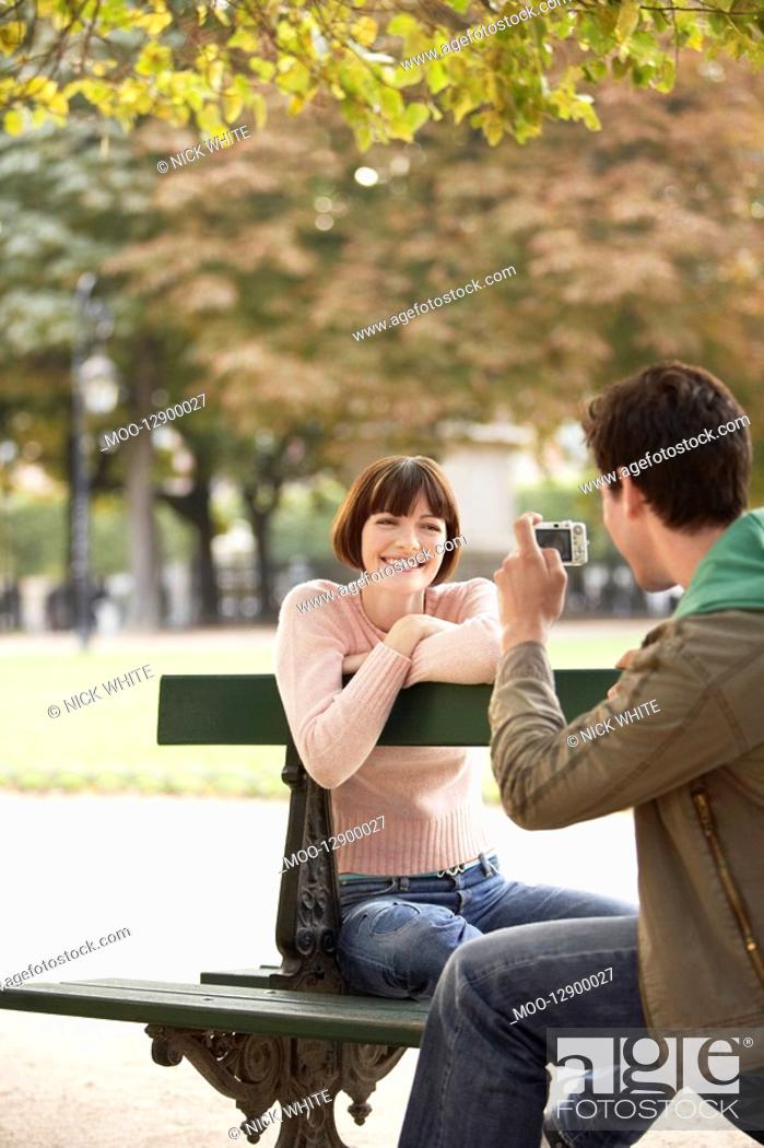 Stock Photo: Young man photographing young woman on bench in park.