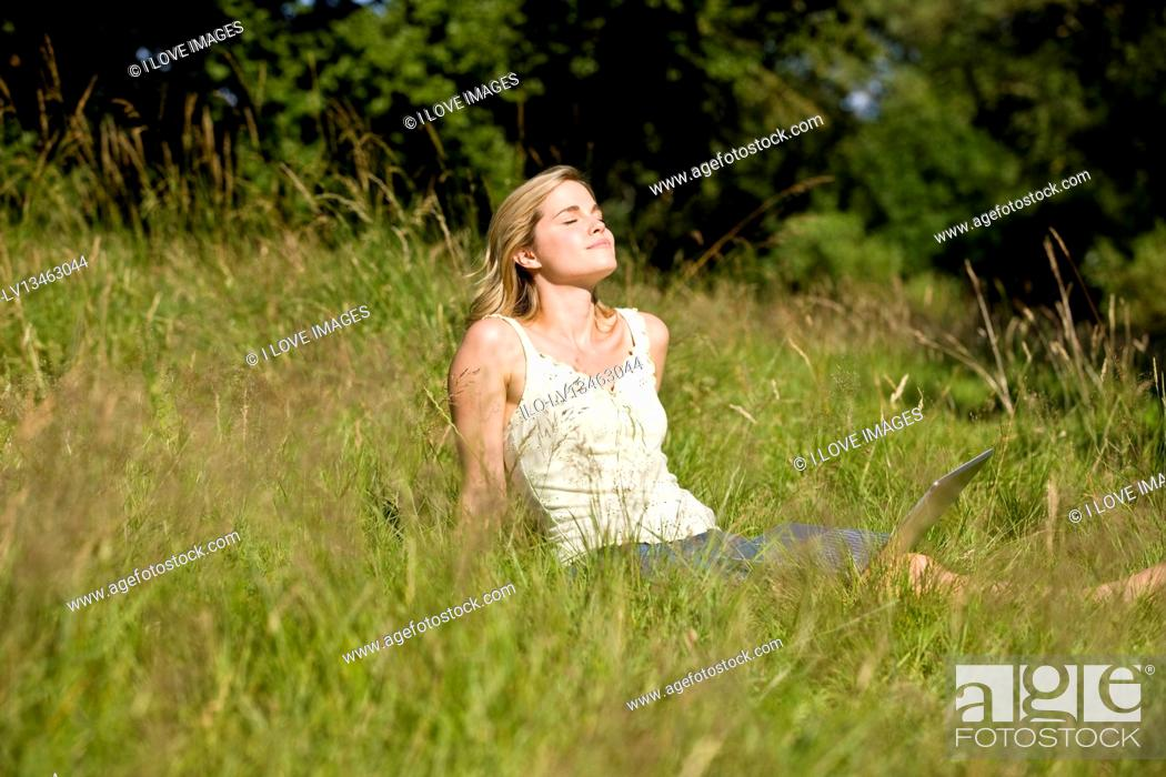 Stock Photo: A young woman sitting on the grass with a laptop, enjoying the sun.
