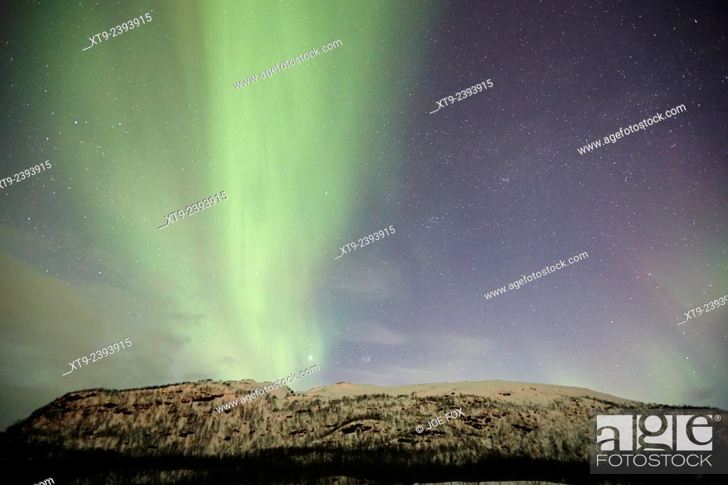 Stock Photo: view of thick green band of northern lights aurora borealis near tromso in northern norway europe.