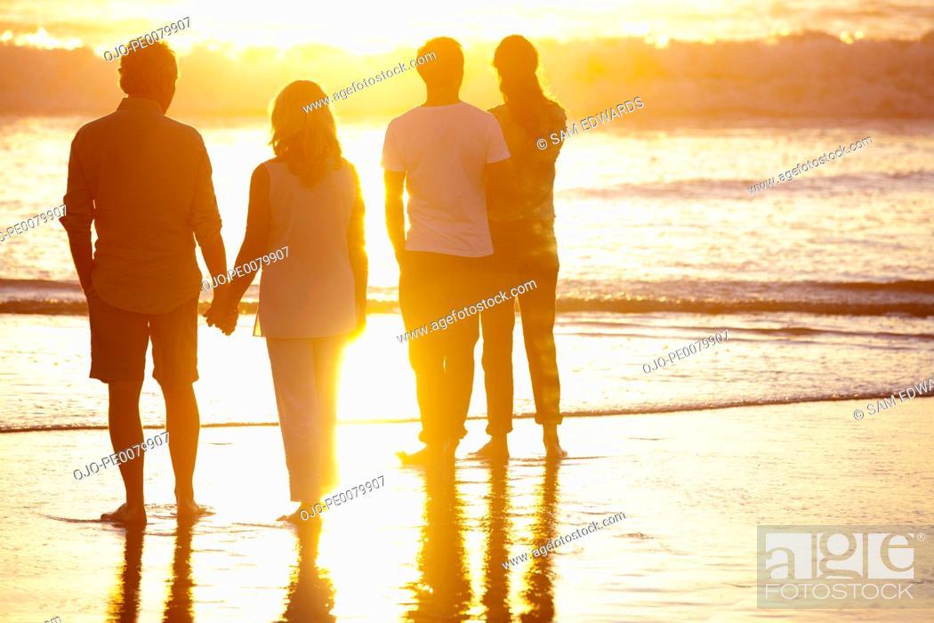 Stock Photo: Couples watching sunset on beach.
