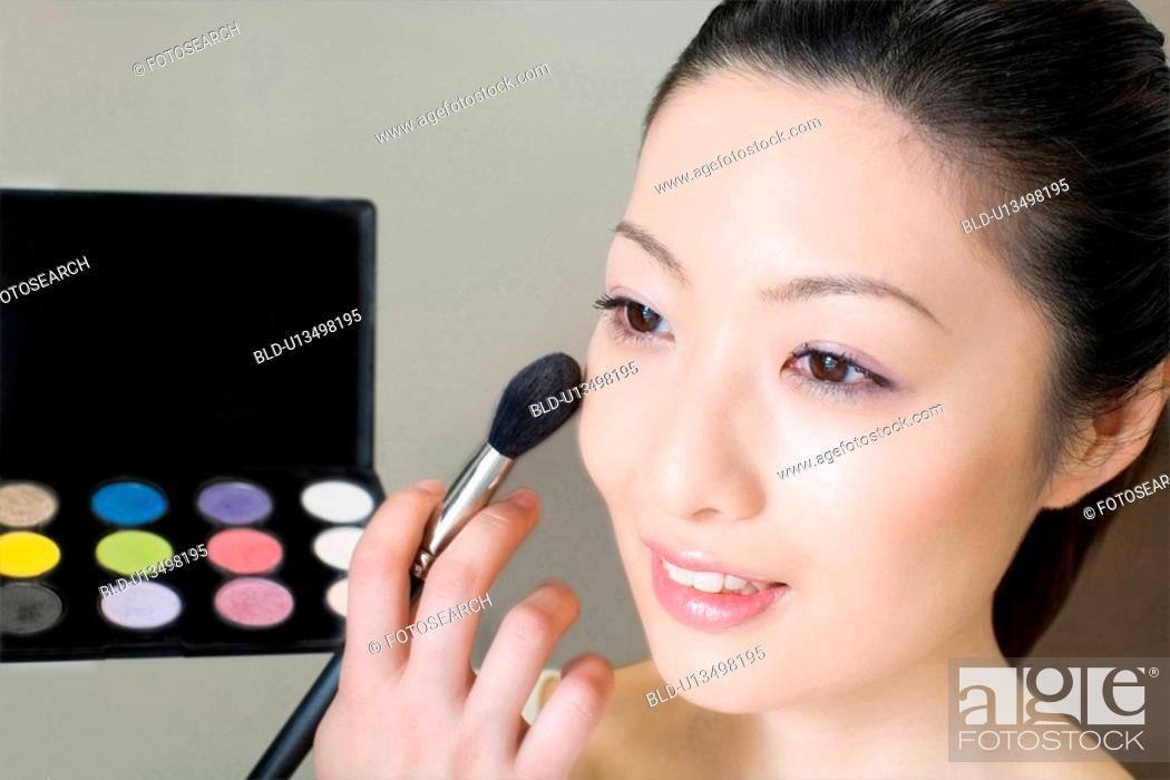 Stock Photo: Making up woman.