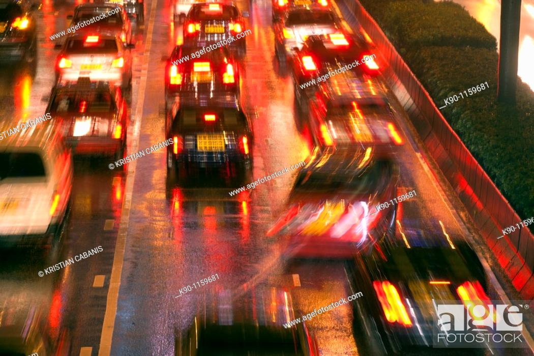 Stock Photo: Blurred image of a traffic jam with cars seen from behind with their red lights and reflections on the wet street after a heavy rain at night, Central.