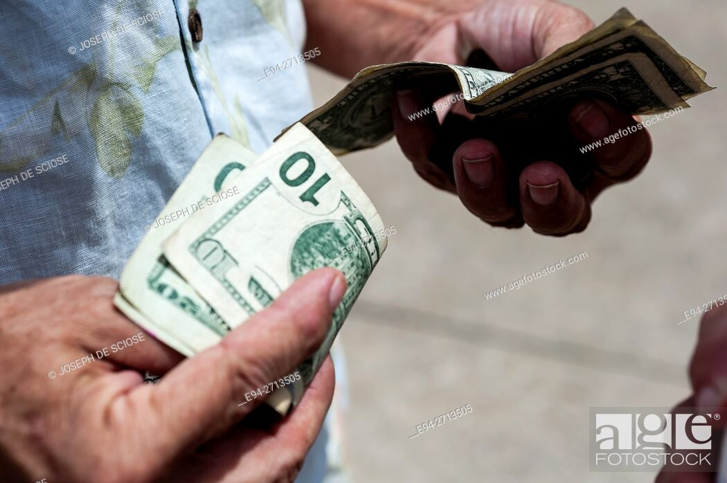 Stock Photo: Various denominations of U.S. currency being held in a man's hands.