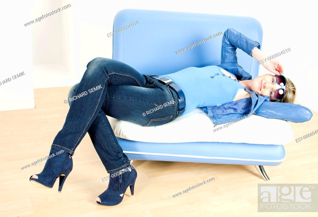 Stock Photo: woman wearing blue clothes lying on sofa.