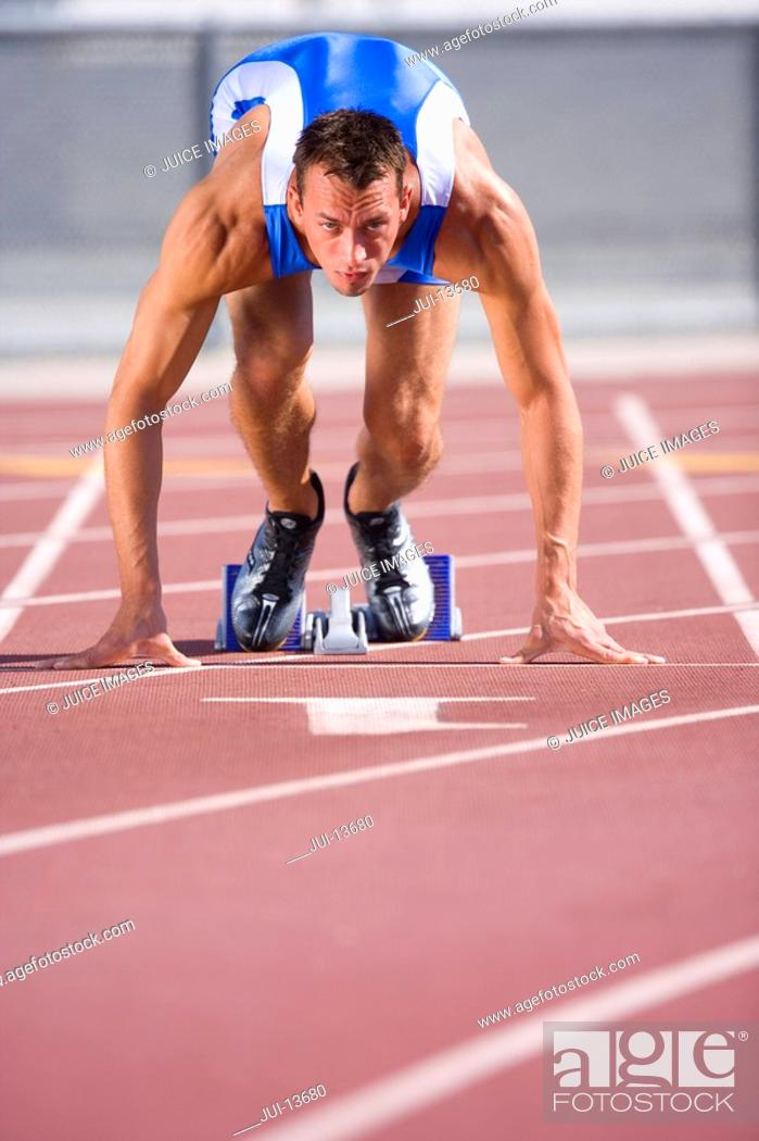 Stock Photo: Male athlete in starting blocks, portrait, low angle view.