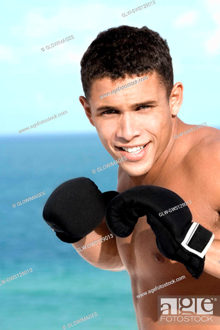 Stock Photo: Portrait of a young man wearing boxing gloves.