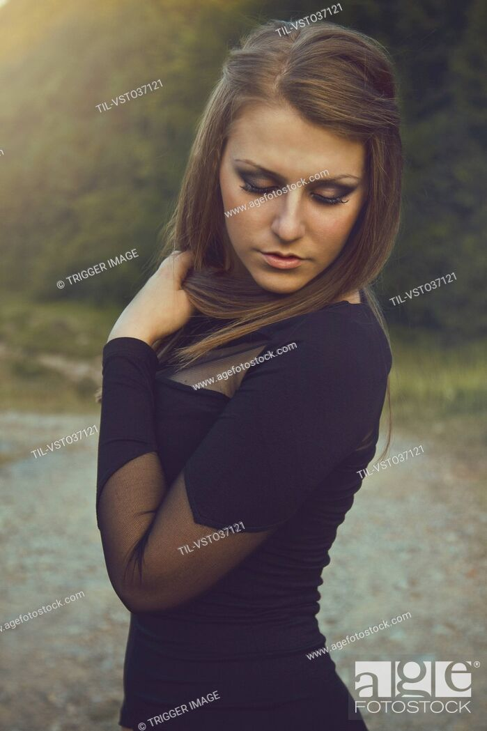 Stock Photo: Elegant Young Woman wearing black dress looking down.