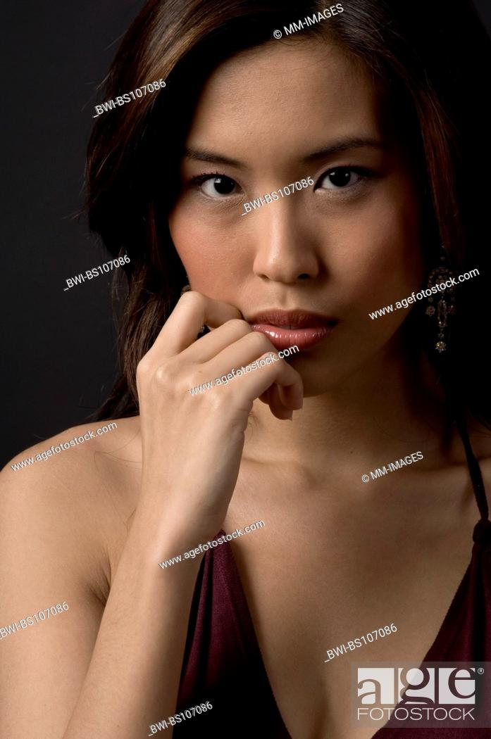 Stock Photo: A beautiful asian woman with hand on chin.