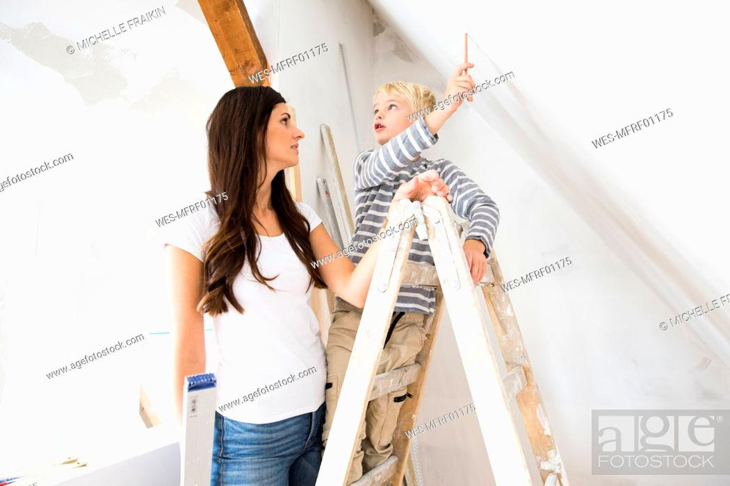 Stock Photo: Mother and son working on loft conversion.