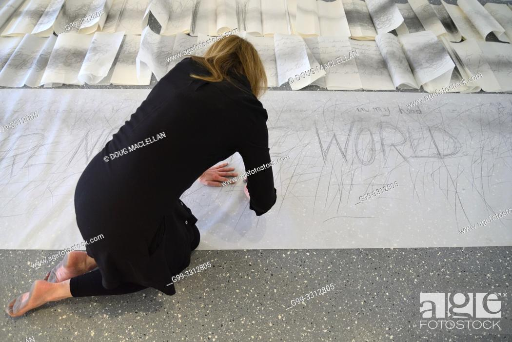 Stock Photo: A woman artist aged 50 to 55 years old creates performance art that incorporates drawing, text, and walking.