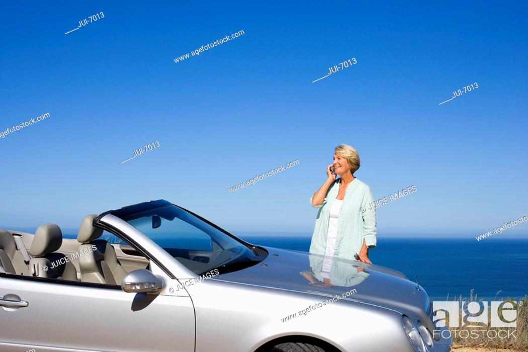 Stock Photo: Senior woman standing beside parked convertible car on clifftop overlooking Atlantic Ocean, using mobile phone, smiling, side view.