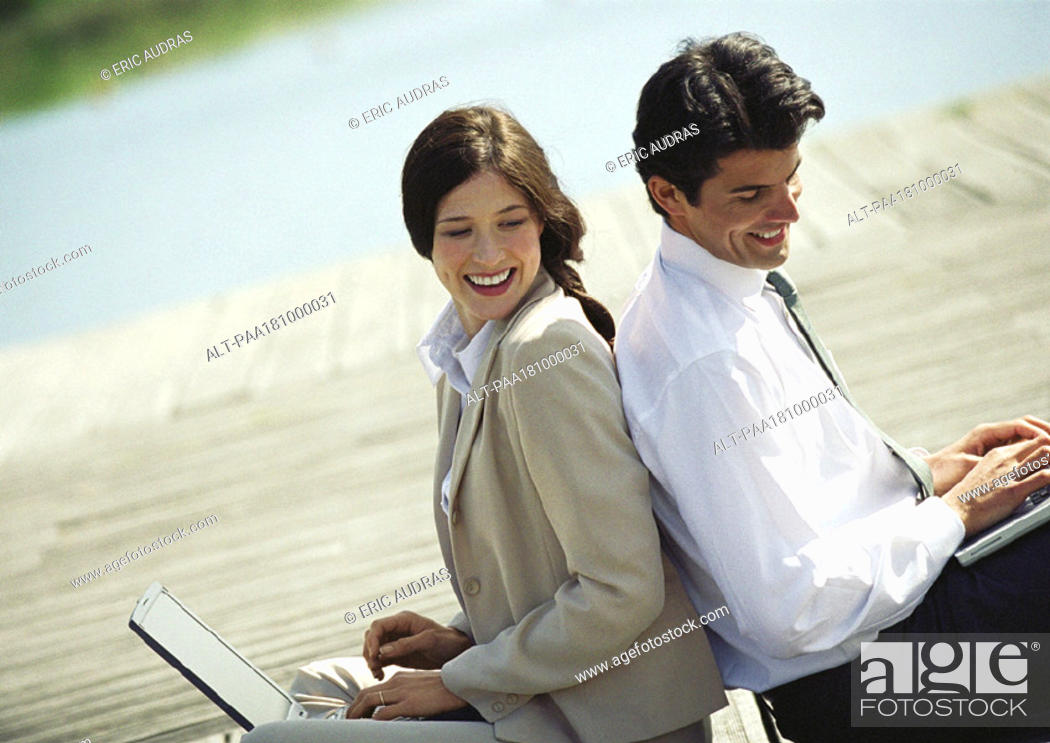 Stock Photo: Businessman and woman back to back with laptop computers, waist up, tilt.