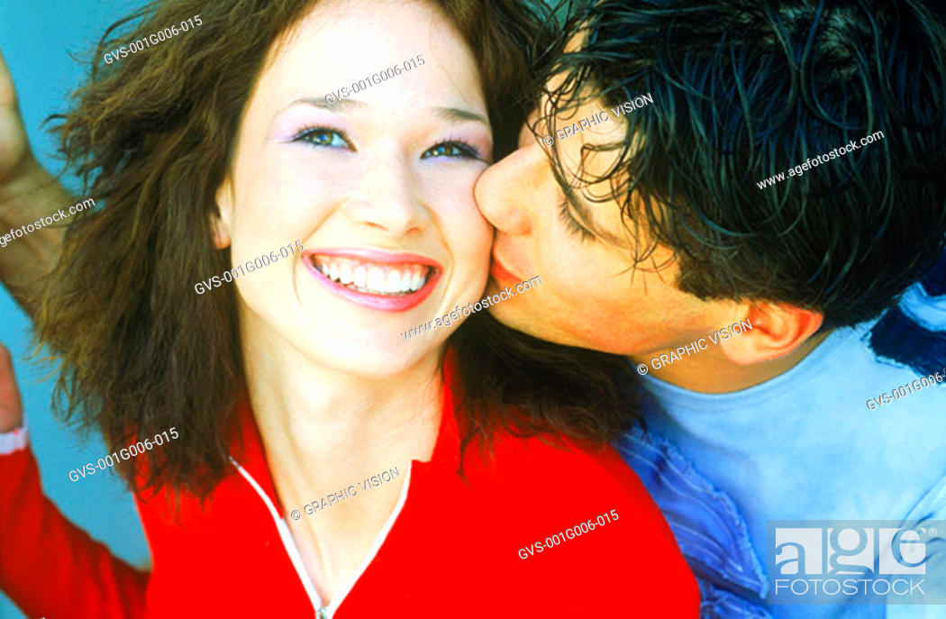 Stock Photo: Close-up of a young man kissing a woman on the cheek.
