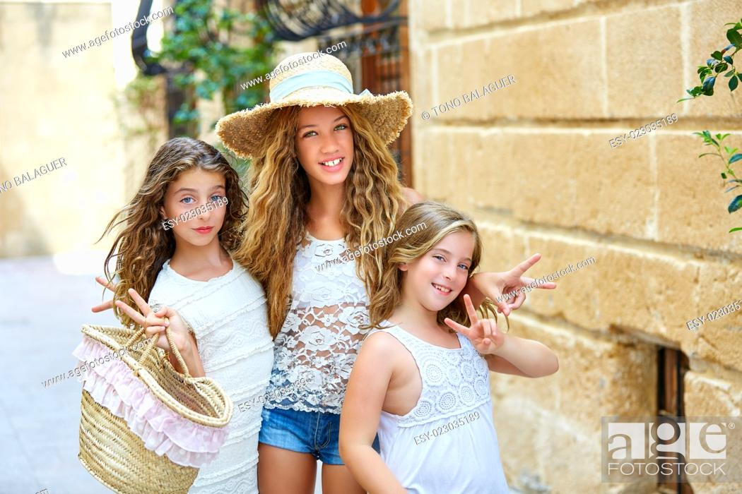 Stock Photo: Tourist kid girls group in mediterranean white old town of Spain.
