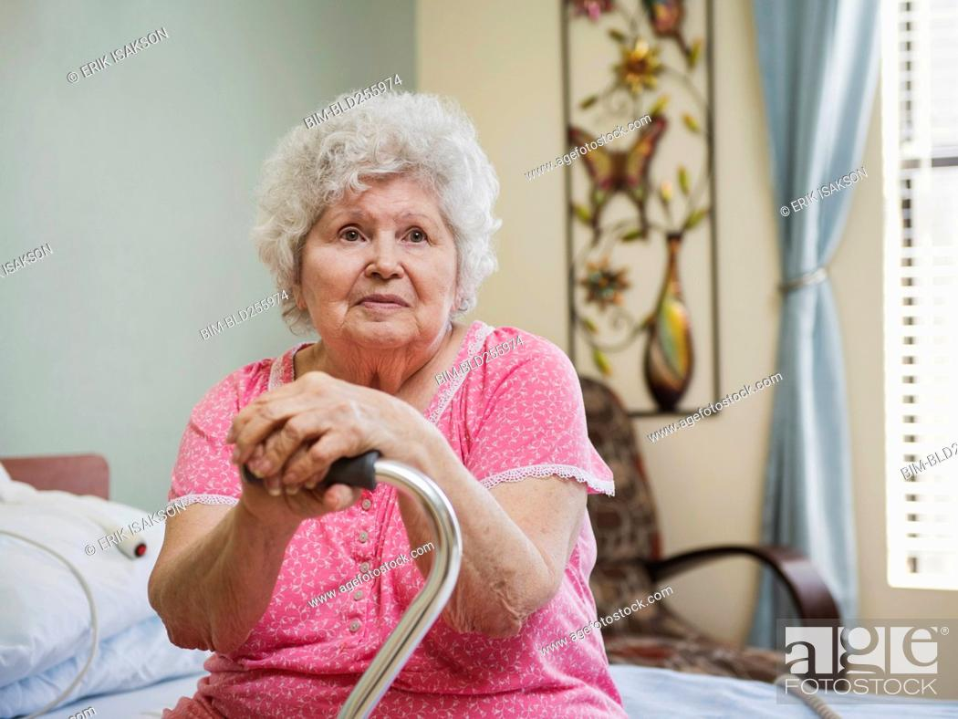 Stock Photo: Serious Caucasian woman sitting on bed leaning on cane.