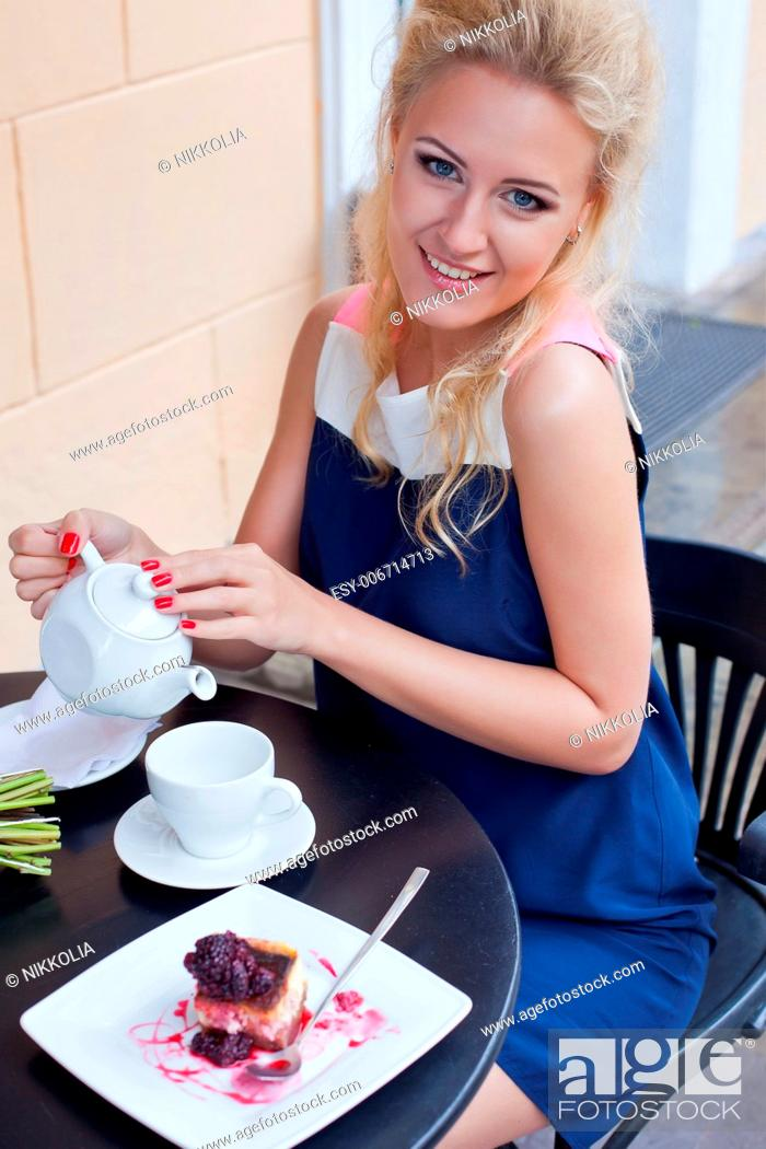 Stock Photo: a beautiful young blond girl with blue eyes in summer dress at the table in pavement cafe is going to pour tea into the cup.