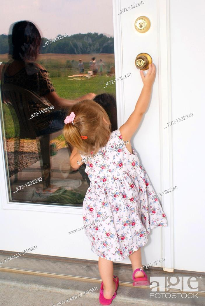 Stock Photo: Unsupervised child tries to open a door.