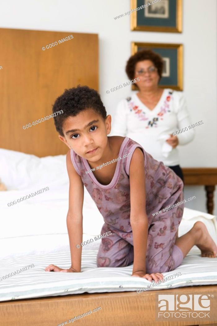 Photo de stock: Young boy crawling on bed.