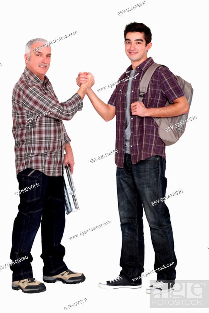 Stock Photo: Manual worker welcoming intern.
