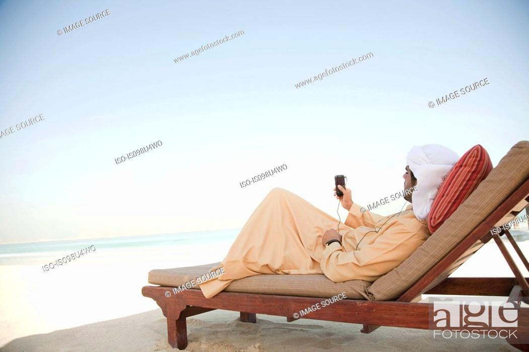 Stock Photo: Middle Eastern man listening to music on mobile phone.