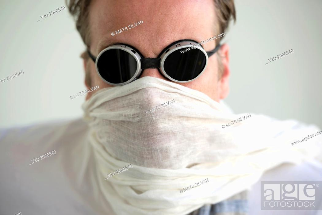 Stock Photo: Man with sunglasses and a scarf cover his face.