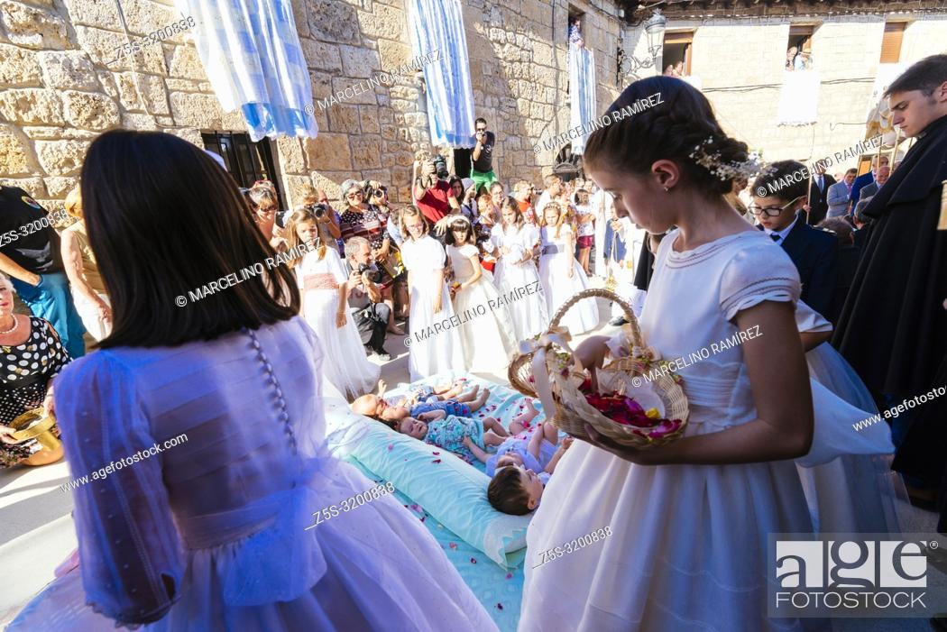 Stock Photo: Procession of the Colacho. Girls who have made First Communion that year throw petals of roses on babies. Castrillo de Murcia, Burgos, Castilla y Leon, Spain.