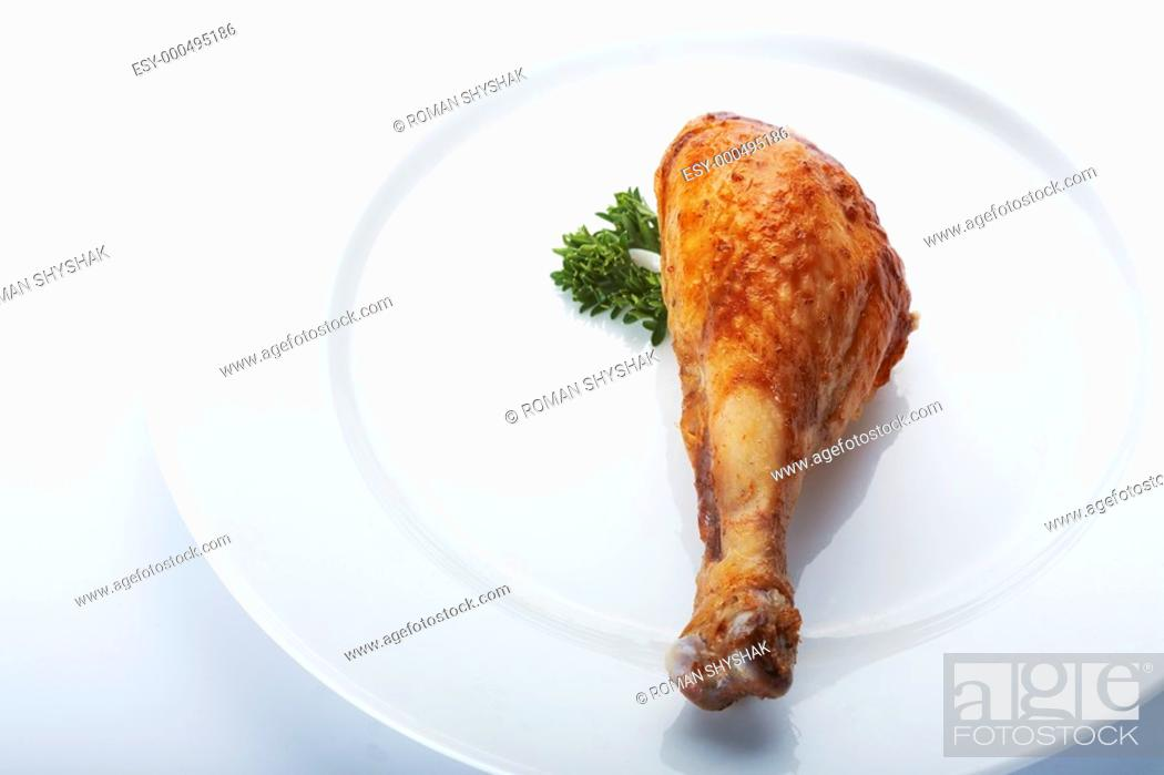 Stock Photo: Closeup picture of roasted chicken leg on the white plate.