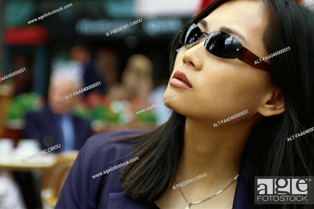Stock Photo: Woman wearing sunglasses, looking up.