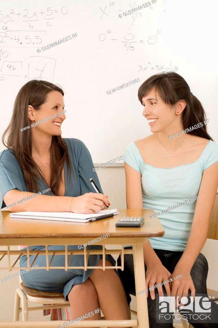 Stock Photo: Teenage girl sitting in a classroom with her female teacher and smiling.