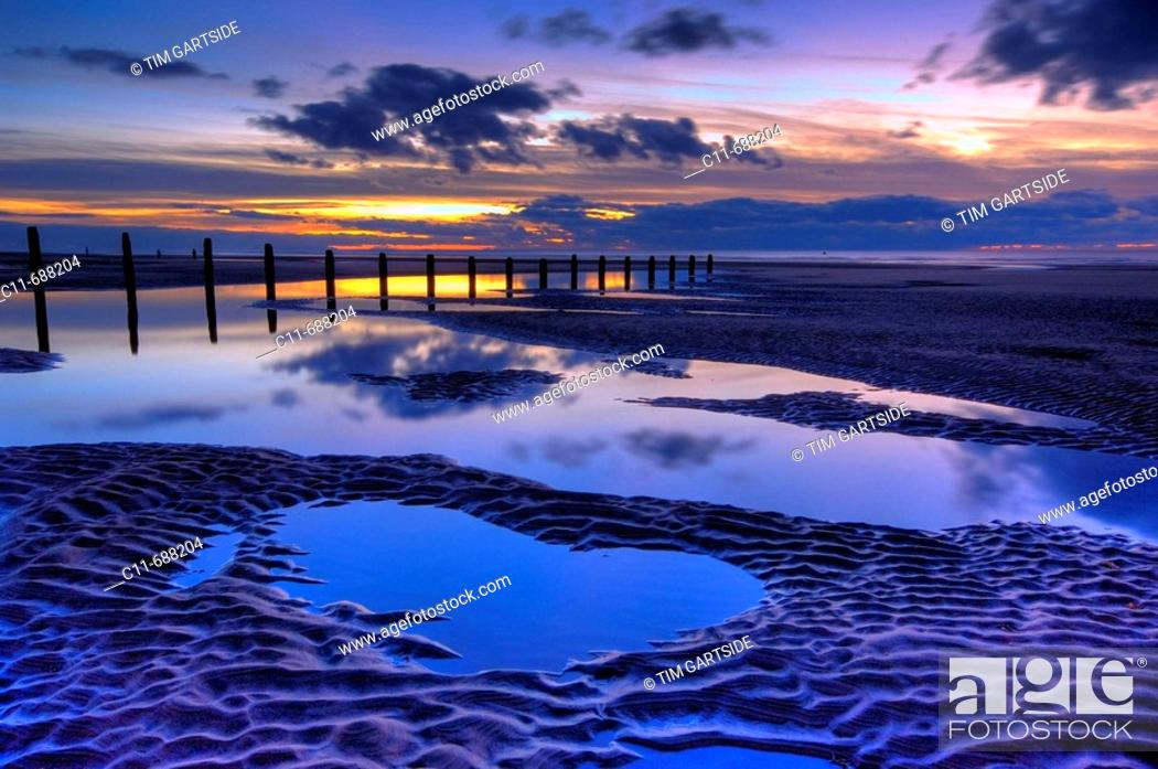 Imagen: beach and wooden groyne at sunset with large pools of water and cloud reflections blackpool lancashire england uk europe.