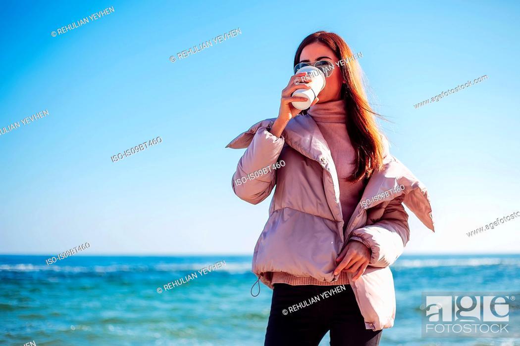 Stock Photo: Stylish mid adult woman on beach drinking takeaway coffee, Odessa, Odeska Oblast, Ukraine.