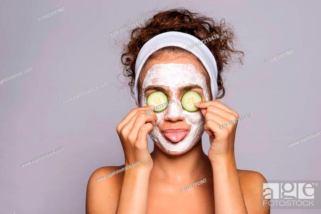 Stock Photo: A portrait of a young woman with face mask and cucumber in a studio, beauty and skin care concept.