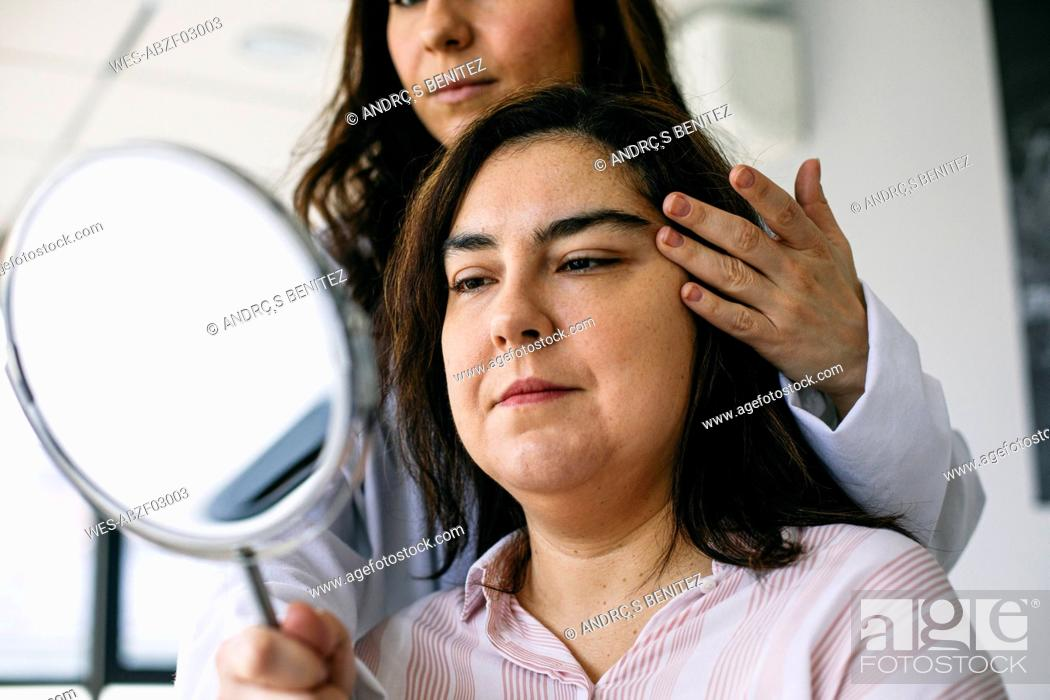 Stock Photo: Cosmetic surgeon holding mirror and talking to patient in medical practice.