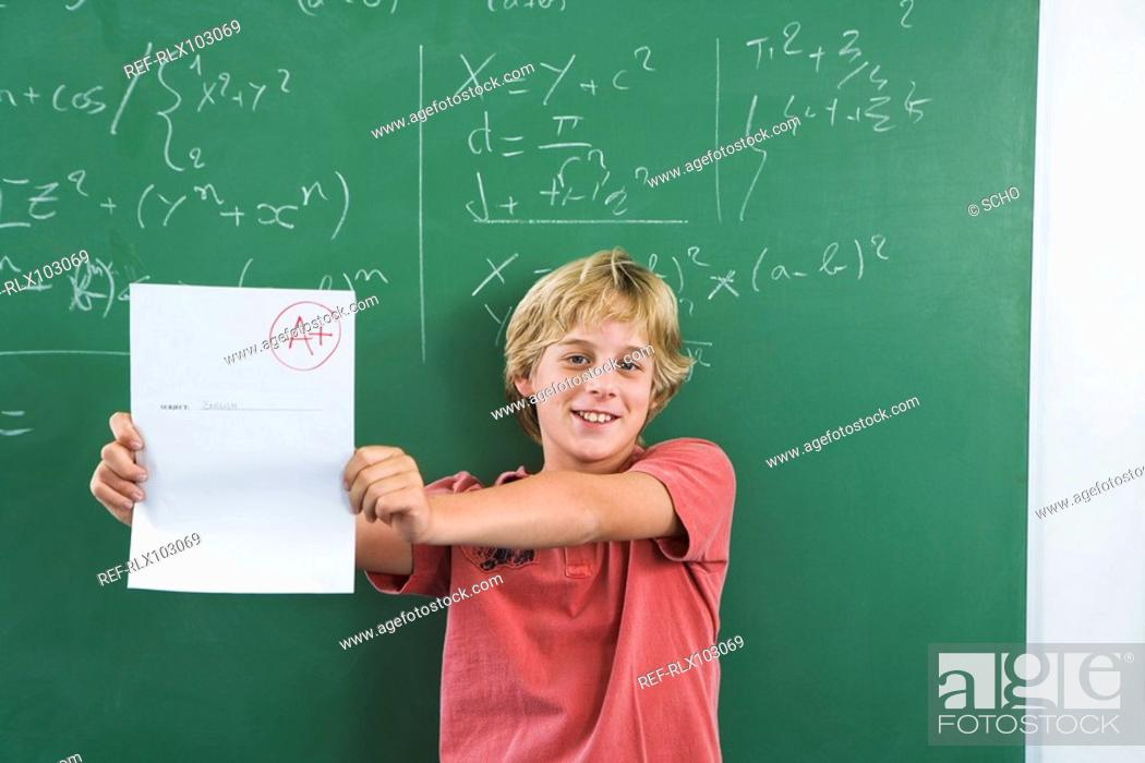 Stock Photo: Boy 10-13 holding up test paper with A+ mark on it, in front of blackboard.