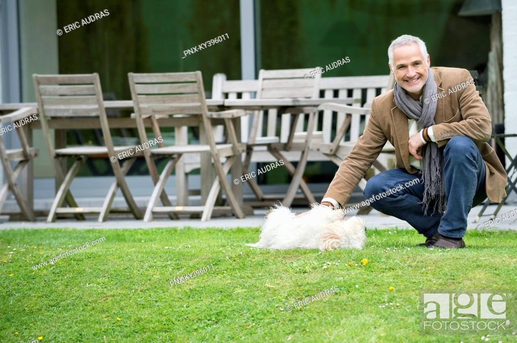 Stock Photo: Man playing with his pets in a garden.