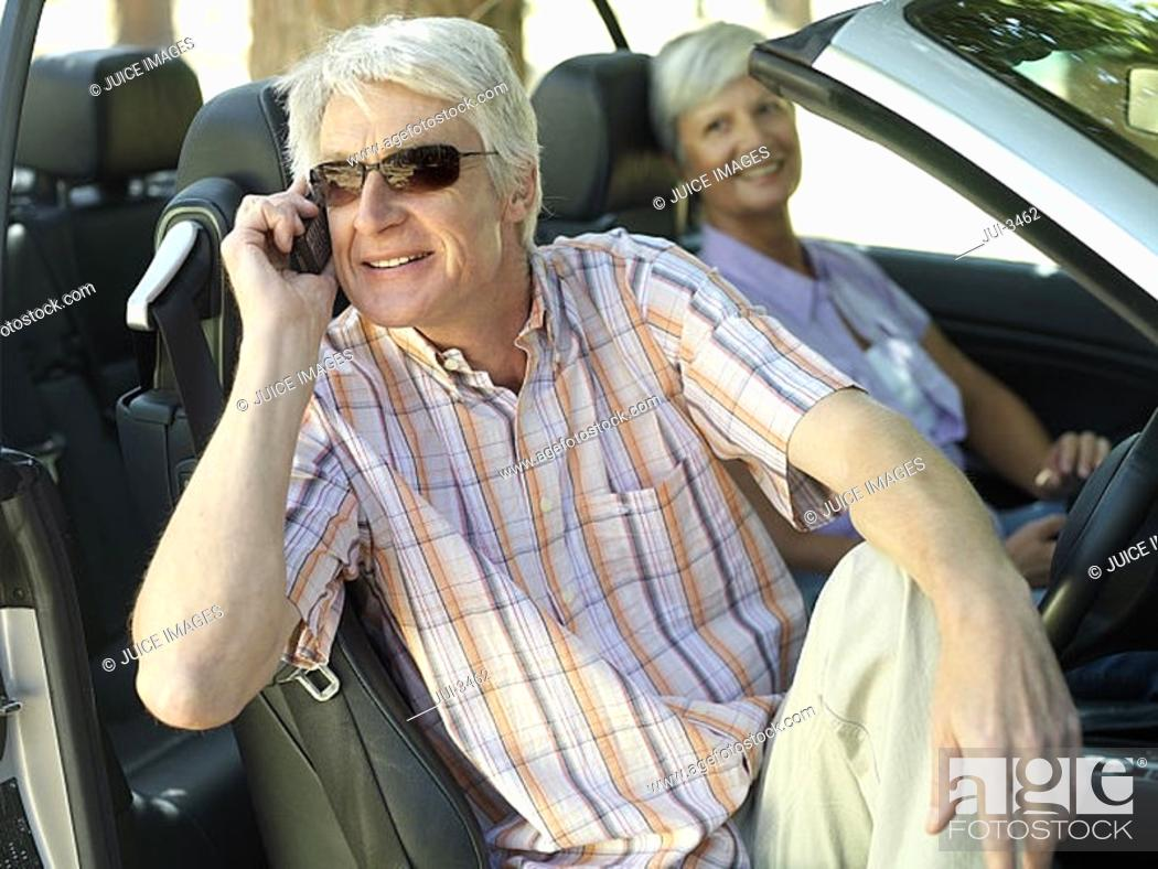 Stock Photo: Senior couple sitting in convertible car, man in sunglasses using mobile phone, smiling, side view.