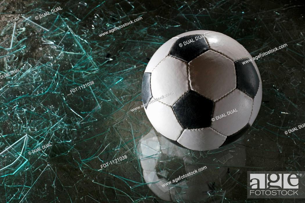 Stock Photo: A soccer ball on broken glass.