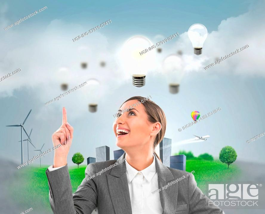 Stock Photo: Ecology ideas concept. Businesswoman standing in front of cityscape with lamp overhead.