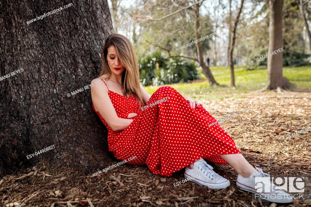 Imagen: Young serious blond woman sitting near tree with red long dress.