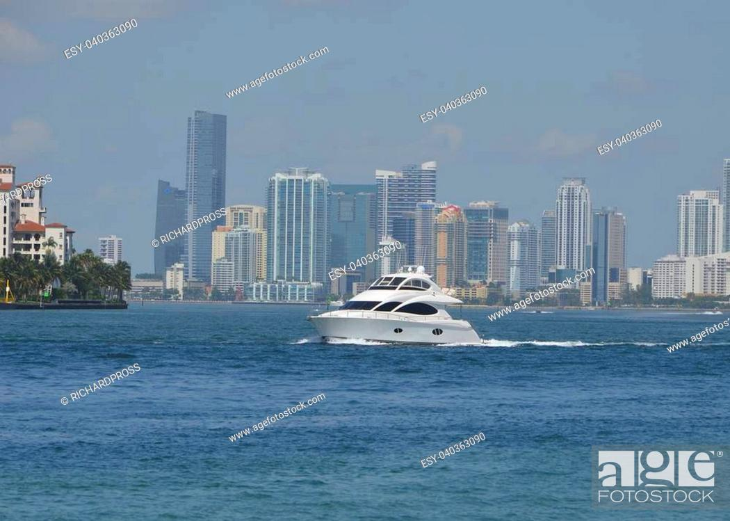 Stock Photo: Small motor yacht on biscayne bay with downtown miami skyline in the background.