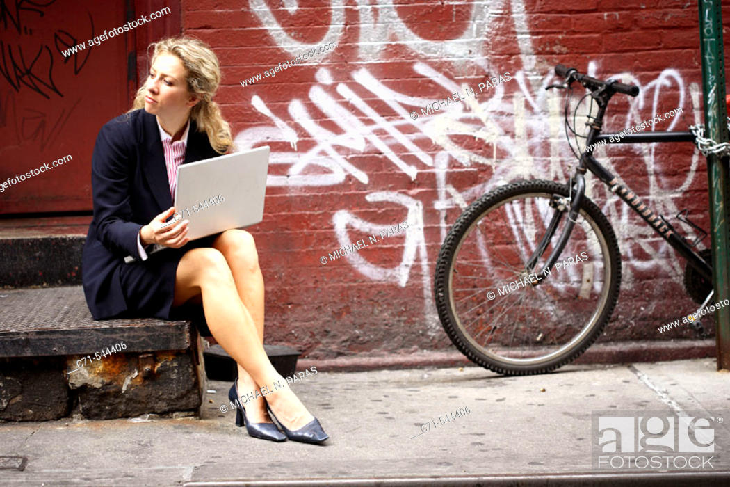 Stock Photo: Caucassian businesswoman working on laptop sitting on a stoop on a public street.