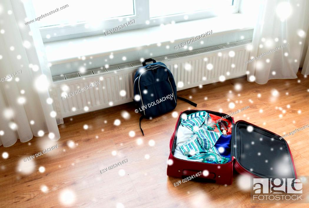 Imagen: vacation, travel, tourism and objects concept - close up of bag with beach clothes and backpack on floor at home or hotel room.