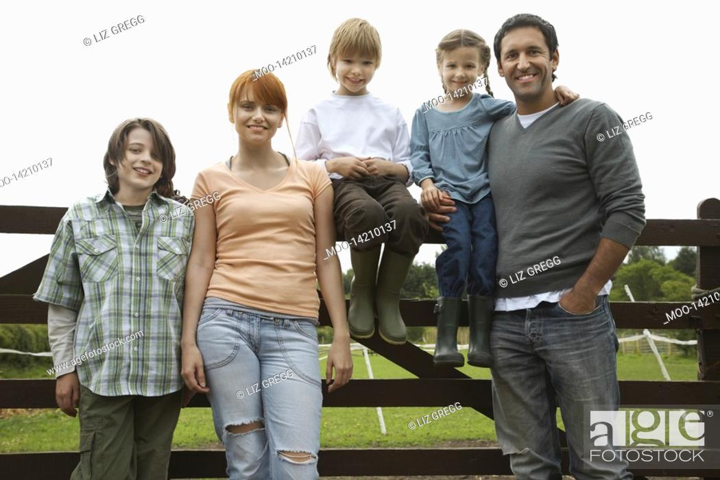 Stock Photo: Parents with three children 5-9 by fence in countryside portrait.