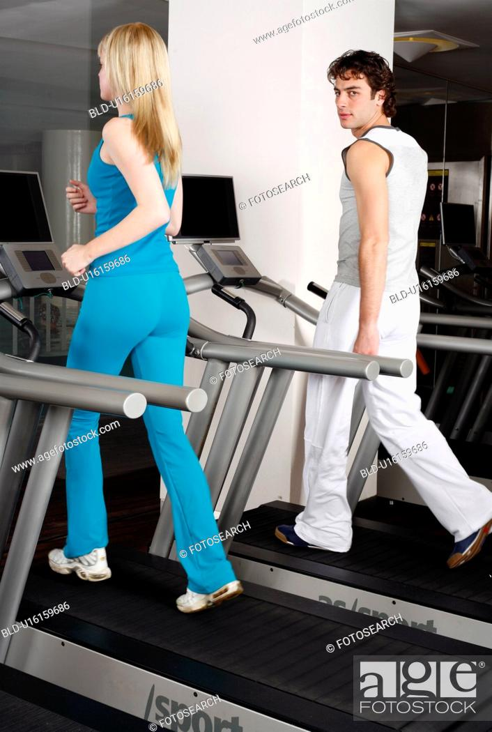 Stock Photo: Young woman and man on treadmill.