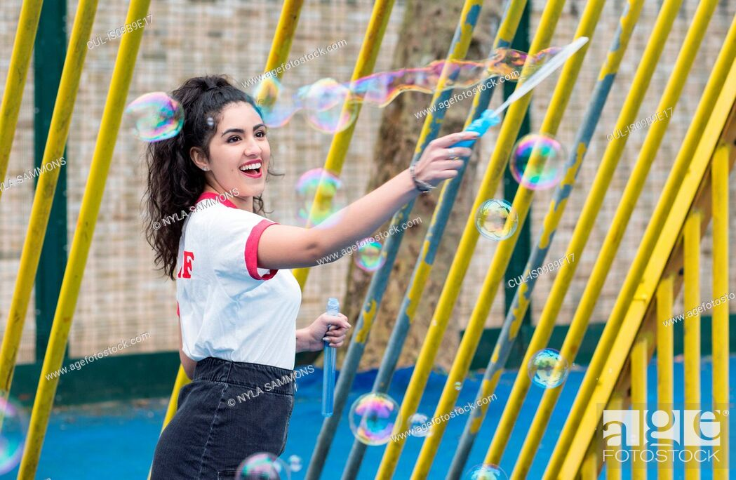 Stock Photo: Enthusiastic young woman in playground making bubbles with bubble wand.