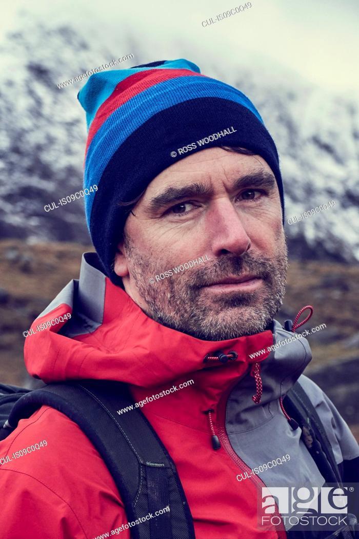 Photo de stock: Male hiker in knit hat by snow capped mountains, close up portrait, Llanberis, Gwynedd, Wales.