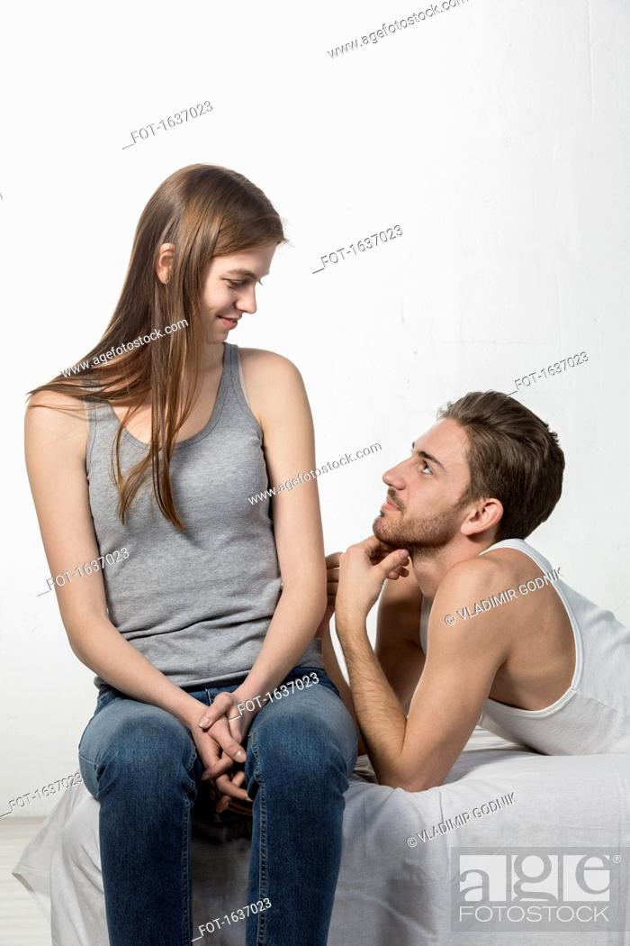 Stock Photo: Smiling man looking at girlfriend while resting on sofa against white background.