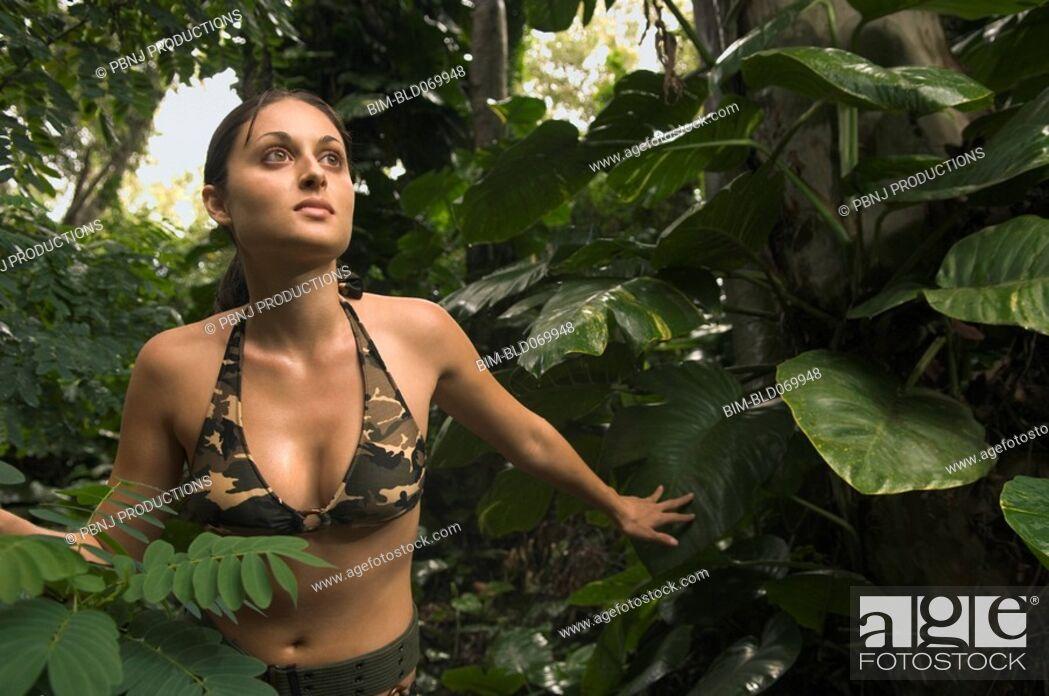 Stock Photo: Hispanic woman wearing camouflage bikini in jungle.