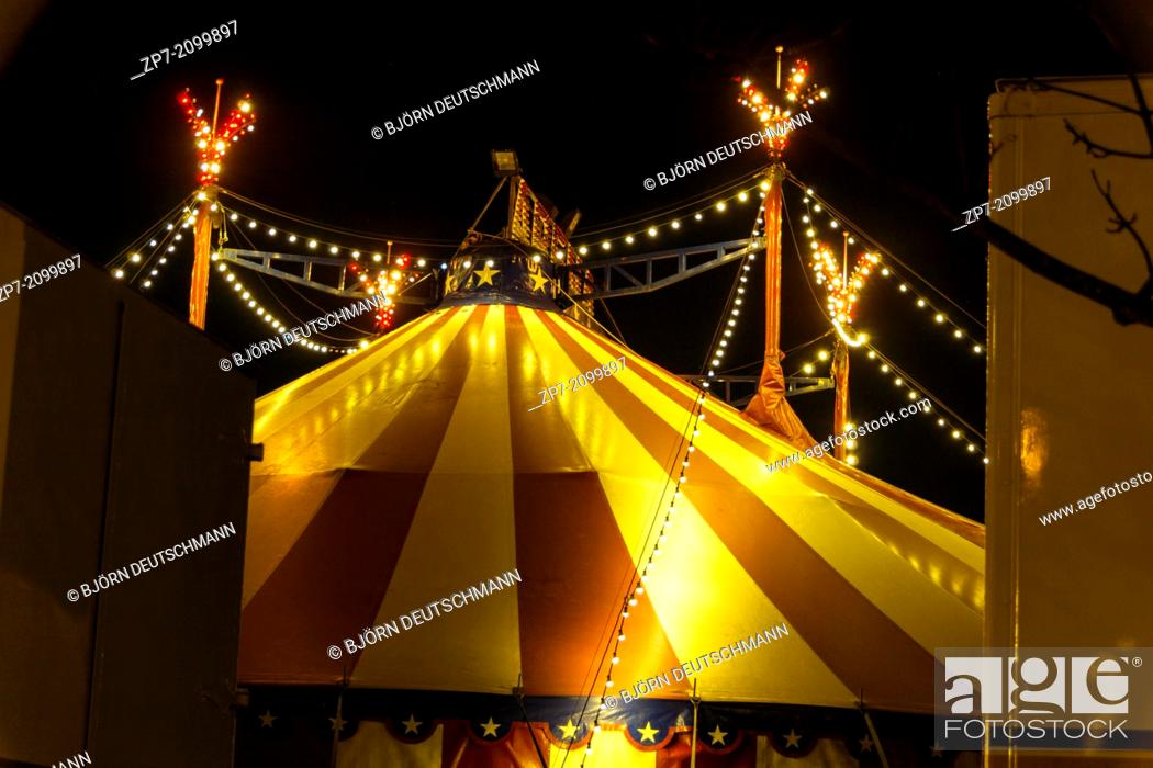 Stock Photo: An illuminated big top at night with the nigh sky at background.